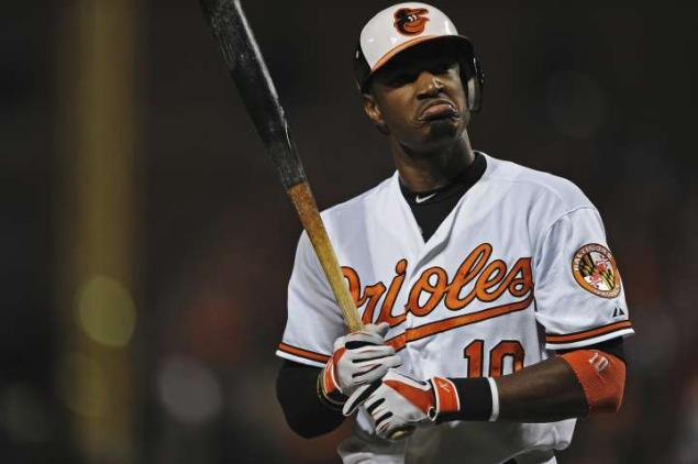 orioles player frowning after hitting baseball