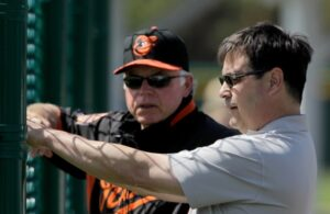 buck showalter standing by fence talking to dan duquette