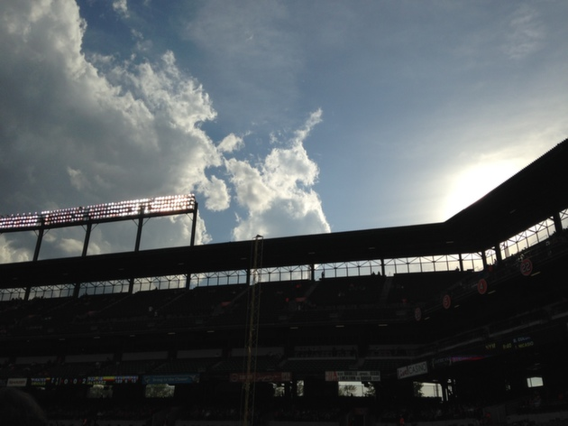 dark upper view of seating at camden yards with clouds and sun