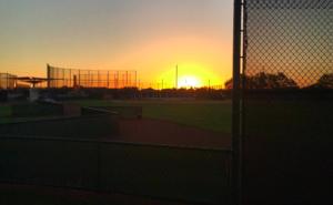 empty baseball field with sun rising