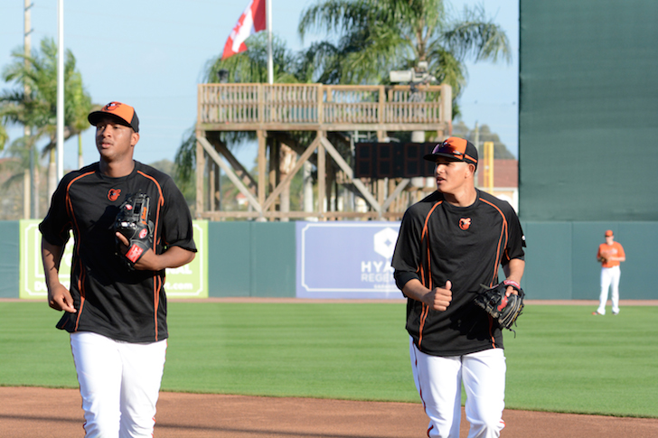 two orioles ball players looking to side while running with gloves