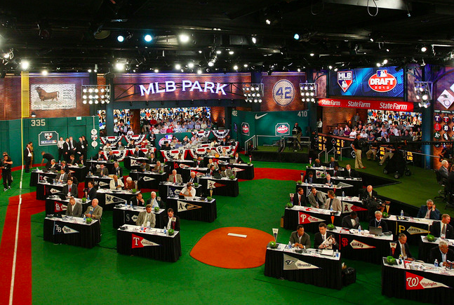men sitting at draft tables in large open room decorated with sports stuff
